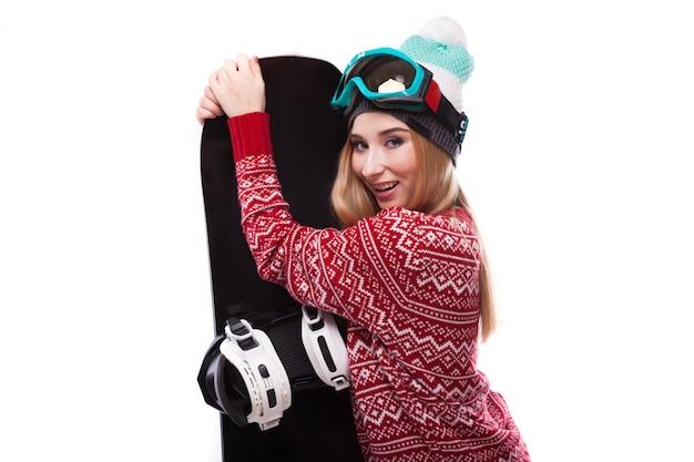 Attraktive junge frau im roten pullover und in den blauen skibrillen halten snowboard