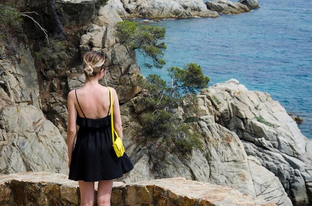 Attraktive junge frau im schwarzen kleid und mit einer gelben kleinen tasche, die an einem sonnigen tag auf einem meer schaut. schlankes mädchen im schwarzen kleid steht gegen rollendes meer und schöne felsen in spanien, lloret de mar.