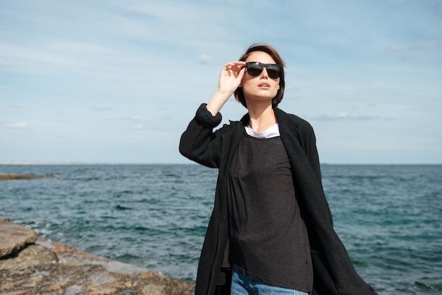 Attraktive junge frau in der sonnenbrille und im schwarzen mantel, die in der nähe des meeres im herbst gehen