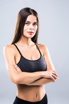 Attraktive junge frau in der sportkleidung, die auf grau aufwirft.