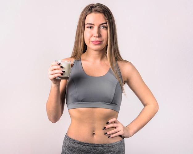 Attraktive junge frau in der sportkleidung mit glas milch