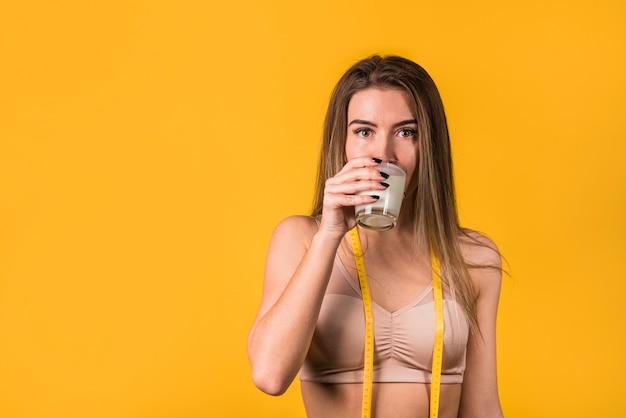 Attraktive junge frau in der sportkleidung mit trinkmilch des bandes