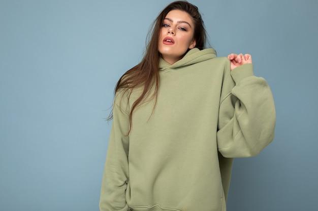 Attraktive junge frau in einem khakifarbenen hoodie. attrappe, lehrmodell, simulation. platz kopieren.
