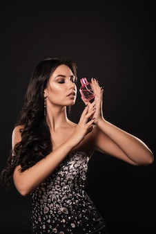 Attraktive junge frau in einem schönen kleid mit parfüm