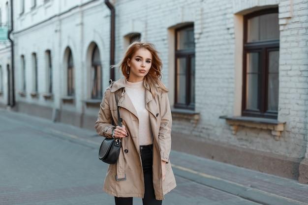 Attraktive junge frau in einem stilvollen hellen mantel in einem weißen t-shirt in jeans mit einer schwarzen ledertasche, die die straße in der nähe eines weißen backsteingebäudes entlang geht. stilvolles blondes mädchen geht durch die stadt.