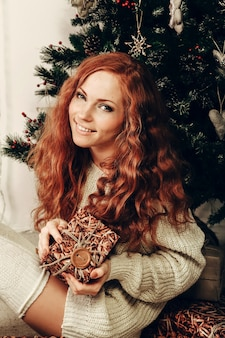 Attraktive junge frau in einer wintermode, die einen weißen wollpullover und eine gestrickte socke trägt. weihnachten.