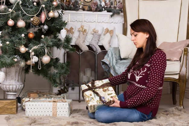 Attraktive junge frau in freizeitkleidung, die auf dem boden in der nähe von weihnachtsbaum sitzt, während sie weihnachtsgeschenkbox hält.