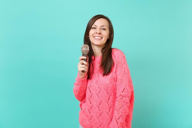 Attraktive junge frau in gestricktem rosa pullover, die in der hand hält und lied im mikrofon singt, isoliert auf blauem türkisfarbenem wandhintergrund, studioporträt. menschen lifestyle-konzept. kopieren sie platz.