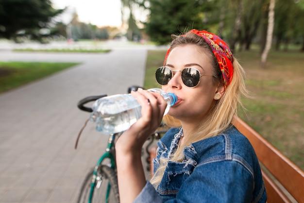 Attraktive junge frau in gläsern, die auf einer bank im park sitzen und wasser von einer flasche trinken.