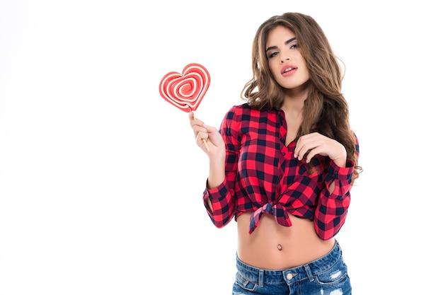 Attraktive junge frau in kariertem hemd und jeans, die herzförmigen lutscher über weißer wand hält
