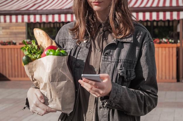 Attraktive junge frau in lässiger kleidung, die recycelbare papiertüte von lebensmitteln hält, die vom lokalen gemüse- und lebensmittelgeschäft oder vom markt gekauft werden.
