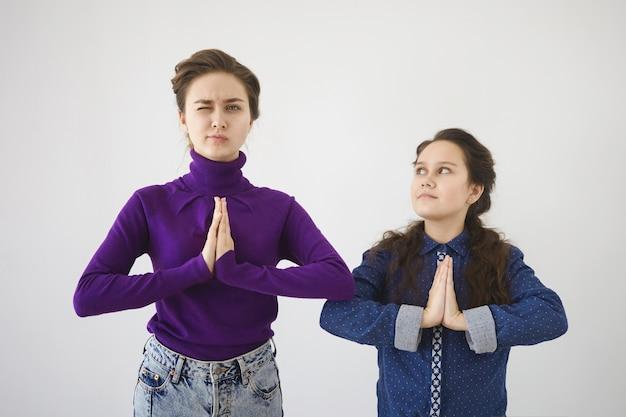 Attraktive junge frau in rollkragenpullover und jeans, die mit ihrer tochter oder kleinen schwester meditation im studio üben
