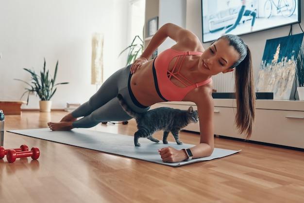 Attraktive junge frau in sportkleidung, die in plankenposition steht, während die katze beim training zu hause herumläuft