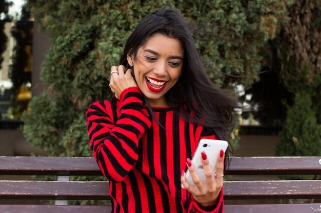 Attraktive junge frau kleidete im rot an, saß in einer bank auf dem park und betrachtete ihr mobiltelefon, lächelte und feierte gute nachrichten. jugendlichkonzept des modernen lebens.
