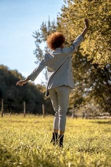 Attraktive junge frau mit afro-haar in einem formellen outfit, die glücklich in einem park in spanien tanzt