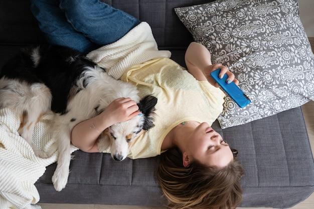 Attraktive junge frau mit australischem schäferhund, der telefon auf couch tippt.