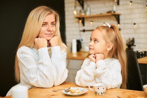 Attraktive junge frau mit blonden langen haaren und ihrer schönen tochter beide in gemütlichen pullovern beim frühstück in der küche am esstisch sitzen, tee trinken, kuchen trinken, hände unter dem kinn halten