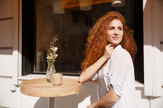 Attraktive junge frau mit dem lockigen haar, das am tisch sitzt