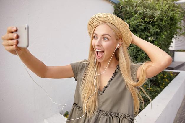 Attraktive junge frau mit langen blonden haaren, die fotos von sich selbst machen, während sie entlang der grünen straße an sonnigem tag gehen und fröhlich zur telefonkamera lächeln