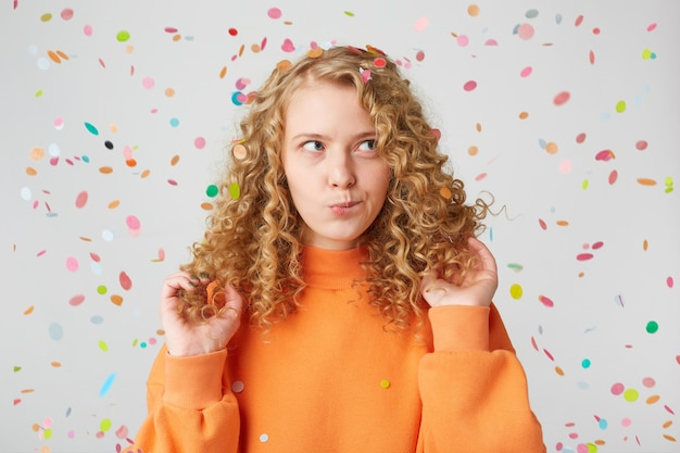 Attraktive junge frau mit nachdenklich nachdenklichem ausdruck, denkt über etwas unter konfetti-regen nach