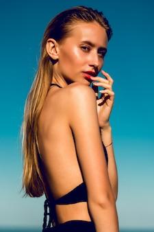 Attraktive junge frau mit perfekt gebräuntem körper, der auf dem strand mit blauem himmel aufwirft.