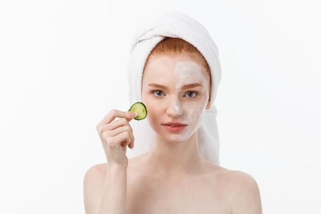 Attraktive junge frau mit schöner sauberer haut. weiße maske und gurken. beauty-behandlungen und kosmetologie spa-therapie.