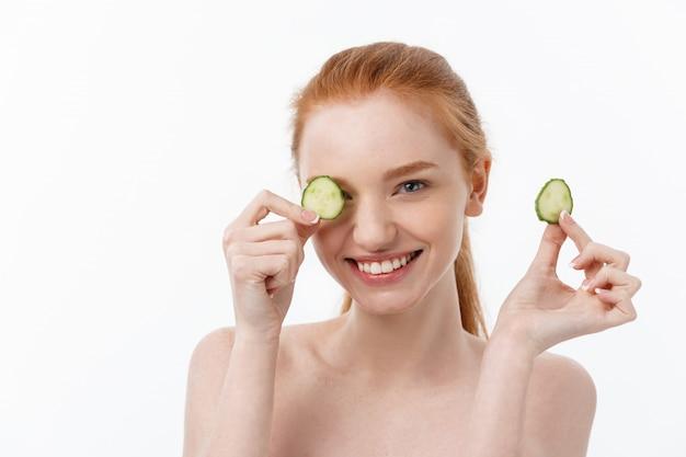 Attraktive junge frau mit schöner sauberer haut. weiße maske und gurken. schönheitsbehandlungen und kosmetologische spa-therapie.