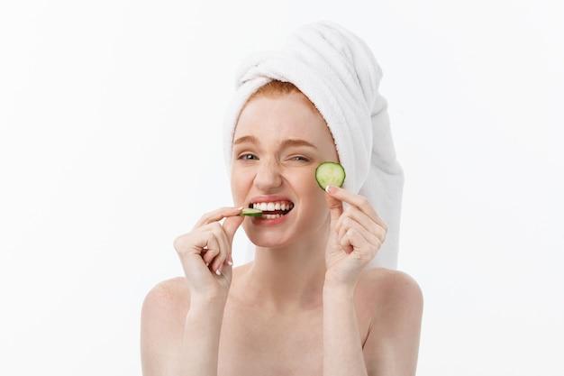 Attraktive junge frau mit schöner sauberer haut. weiße maske und gurken