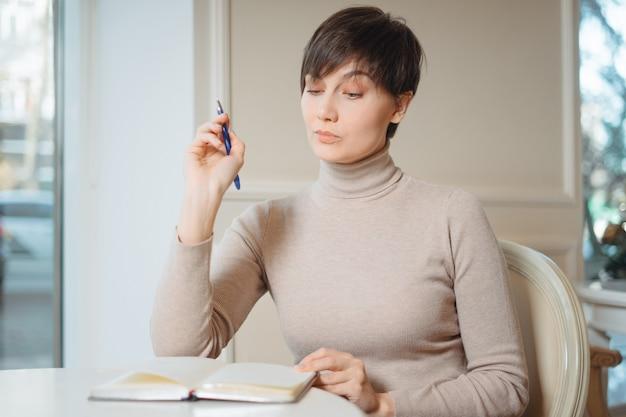 Attraktive junge frau mit stift in der hand, die an pläne denkt und liste schreibt, um im notizblock zu tun, der erholungszeit im stilvollen café genießt