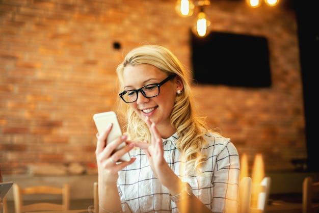 Attraktive junge frau mit welligen blonden haaren ist am telefon