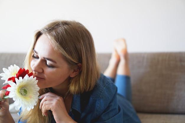 Attraktive junge frau schnüffelt blumenstrauß auf der couch liegen
