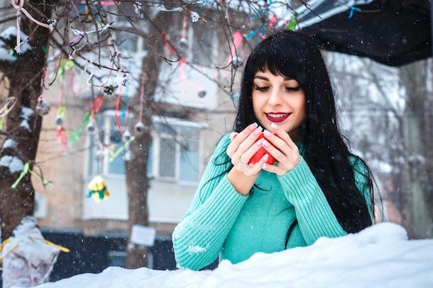 Attraktive junge frau trinkt am verschneiten wintertag einen kaffee im straßencafé