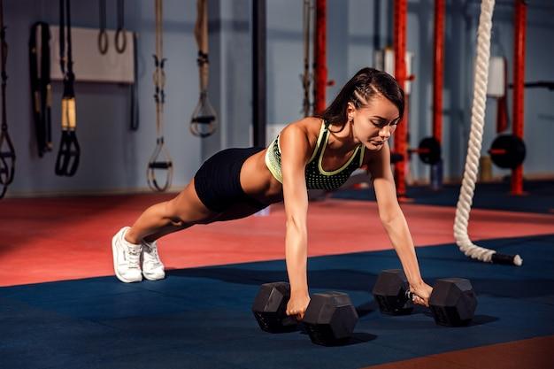Attraktive junge frau tut plankenübung beim ausarbeiten in der turnhalle