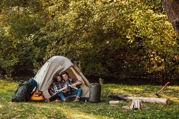 Attraktive junge frau und gutaussehender mann verbringen zeit zusammen in der natur. im touristischen zelt im wald sitzen und tee trinken