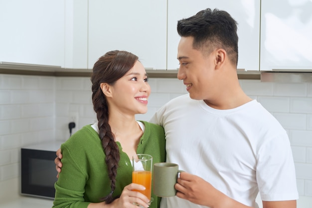 Attraktive junge frau und hübscher mann genießen, zeit zusammen zu verbringen, während sie auf heller moderner küche stehen.