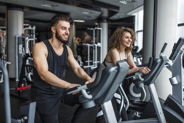 Attraktive junge frau und ihr trainer, die auf dem laufband im fitnessstudio laufen