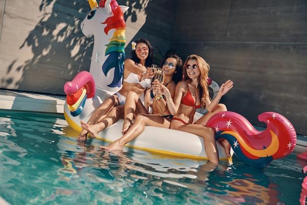 Attraktive junge frauen in badebekleidung, die lächeln und champagner trinken, während sie auf einem aufblasbaren einhorn im schwimmbad im freien schwimmen