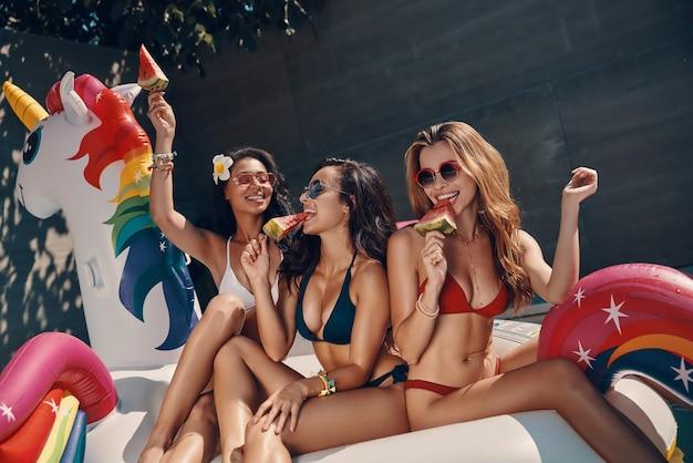 Attraktive junge frauen in badebekleidung lächeln und essen wassermelone, während sie auf einem aufblasbaren einhorn im schwimmbad im freien schwimmen