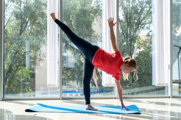 Attraktive junge frauen in sportbekleidung, die yoga-übung in einem yoga nahe fenstern tun. gesundheitskonzept.