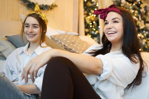 Attraktive junge freundinnen in stilvollen kleidern sitzen zusammen auf dem boden und diskutieren die neuesten nachrichten