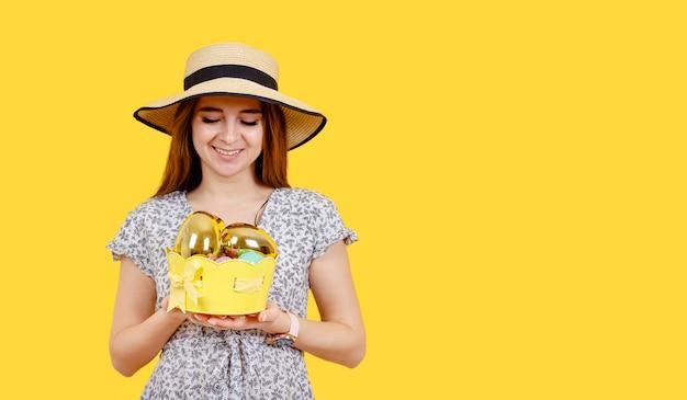 Attraktive junge fröhliche frau mit zahnigem perfektem lächeln, das ostereier hält.