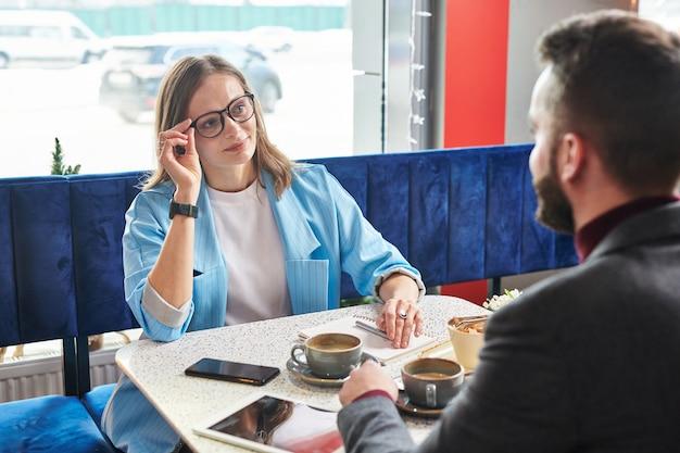 Attraktive junge geschäftsfrau, die brillen anpasst und mit kollege beim treffen im modernen café plaudert