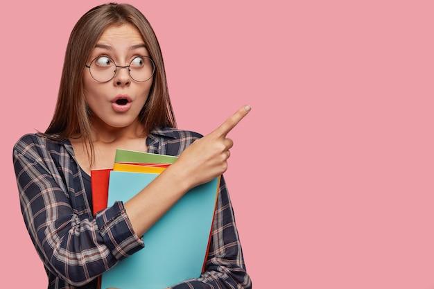 Attraktive junge geschäftsfrau, die gegen die rosa wand mit brille aufwirft