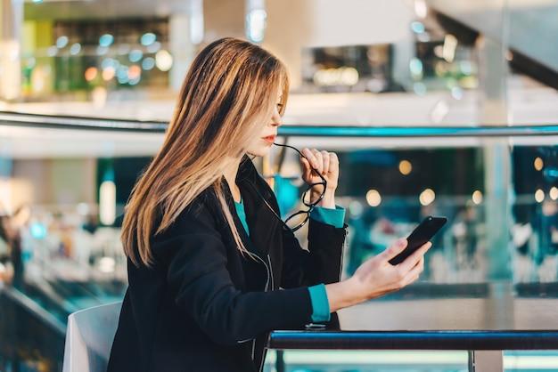 Attraktive junge geschäftsfrau, die ihr handy während der kaffeepause in einem einkaufszentrum durchsucht