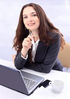Attraktive junge geschäftsfrau, die im hellen büro am laptop arbeitet