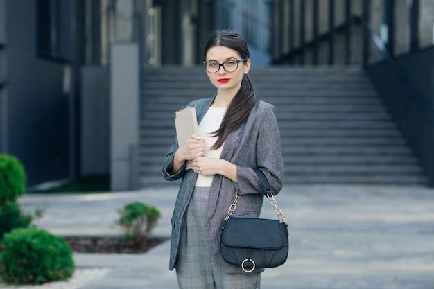 Attraktive junge geschäftsfrau mit brille tragen grauen eleganten anzug. porträt der jungen geschäftsfrau, die brille mit einem ernsten gesicht trägt.