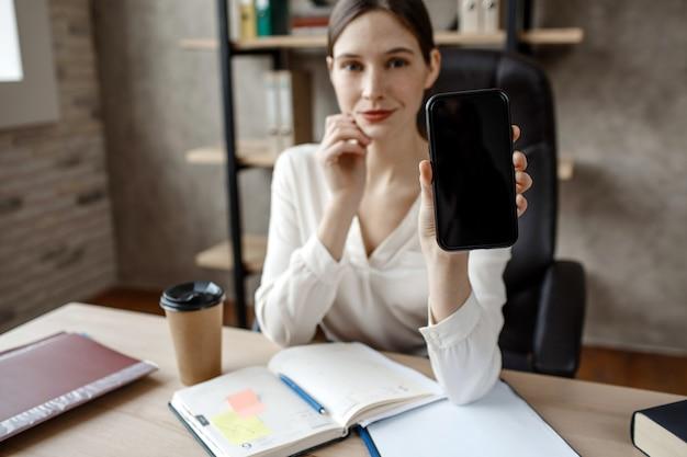 Attraktive junge geschäftsfrau zeigen telefon vor der kamera. sie sitzt am tisch im zimmer. geöffnetes notizbuch und eine tasse kaffee.