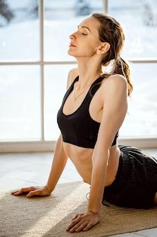 Attraktive junge gesunde frau im sportlichen schwarzen oberteil und in den leggings, die yoga-streckung zu hause tun. gesundes lebensstilkonzept. seitenansicht.