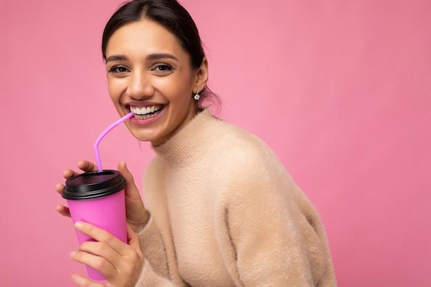 Attraktive junge glückliche lächelnde brünette frau, die alltägliche stilvolle kleidung lokalisiert über bunte hintergrundwand hält, die pappbecher für ausschnitt trinkt tee betrachtet kamera.