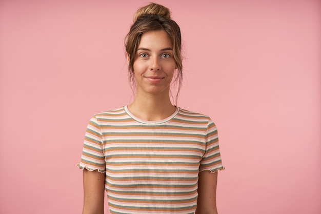 Attraktive junge grünäugige brünette, die sanft lächelt, während sie positiv in die kamera schaut und hände unten hält, während sie über rosa hintergrund steht